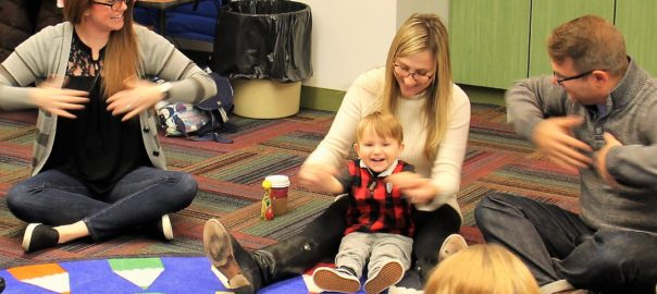 Luke Worgul (center) and his parents, Kristen and John, play a music game with Kaitlin Wade,                    speech language therapist, at DePaul School for Hearing and Speech.